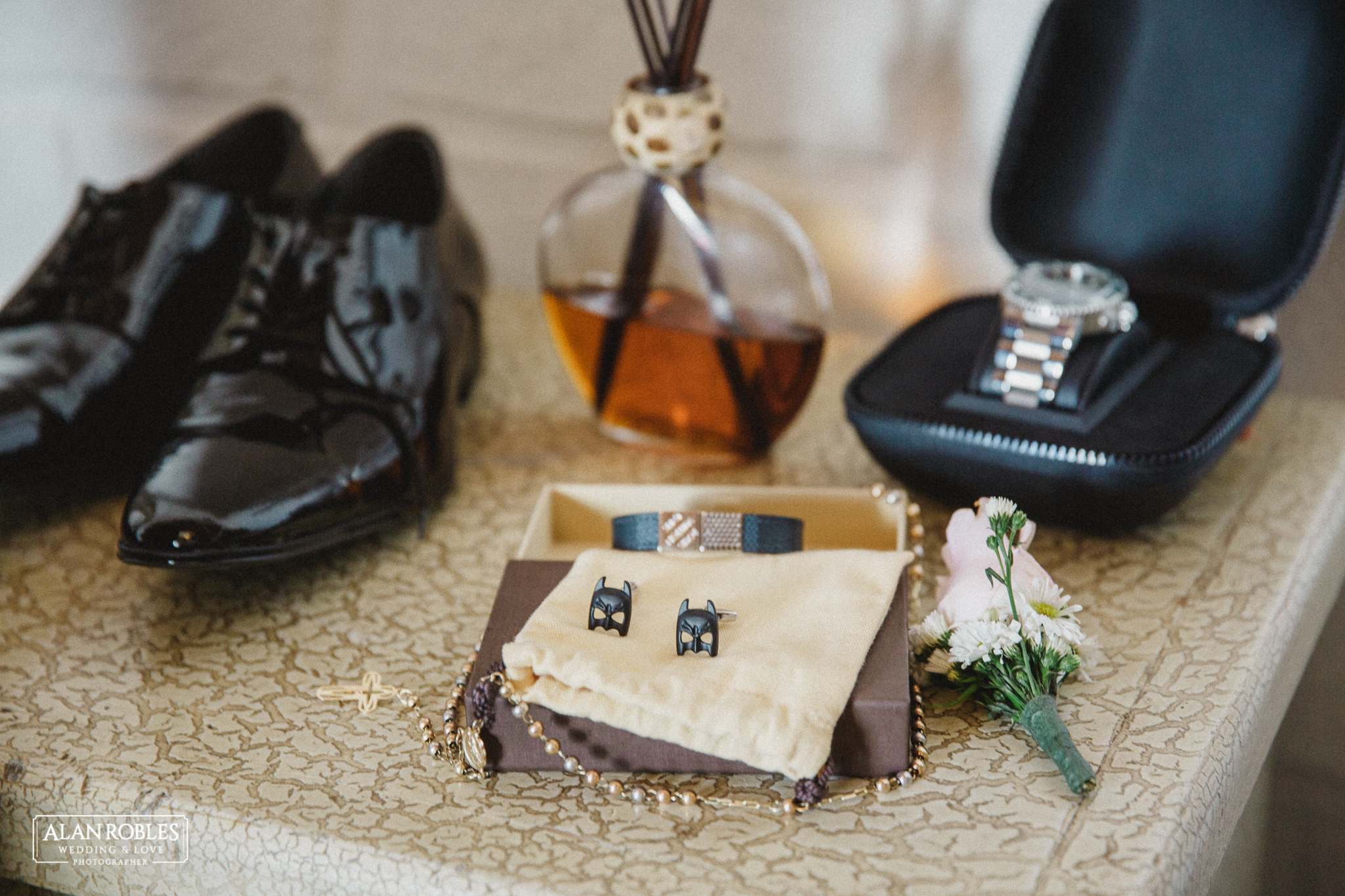 Detalle de los accesorios del novio, botonier, azar, mancuernillas de super heroe batman, zapatos y reloj para la boda. Fotografo de Bodas Alan Robles en Guadalajara.