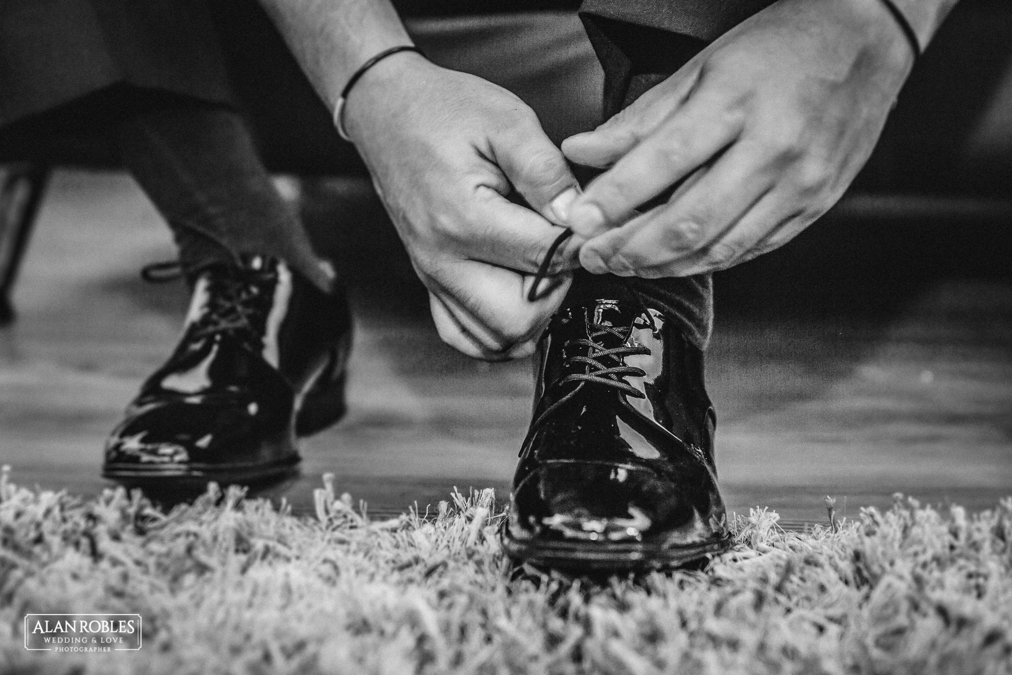 Zapatos del Novio. Getting Ready el dia de la boda, fotografia de bodas en Blanco. Alan Robles, fotografo de Bodas en Guadalajara. Amarrando las agujetas.