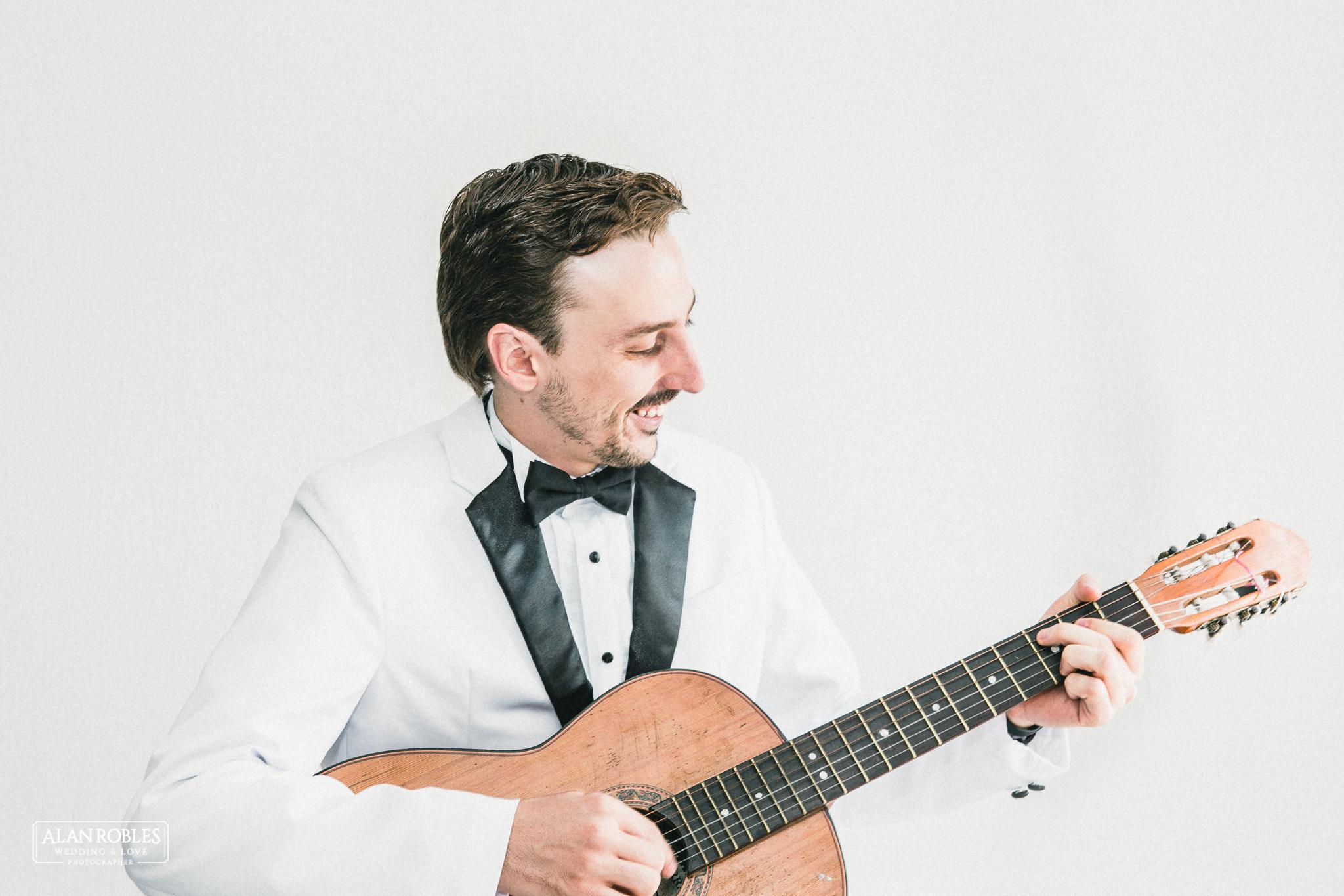 Novio en Getting Ready Tocando la guitarra y cantando, sonriente. Los mejores momentos.. Wedding Moments. El mejor fotografo de bodas en Guadalajara Alan Robles Wedding Photographer.