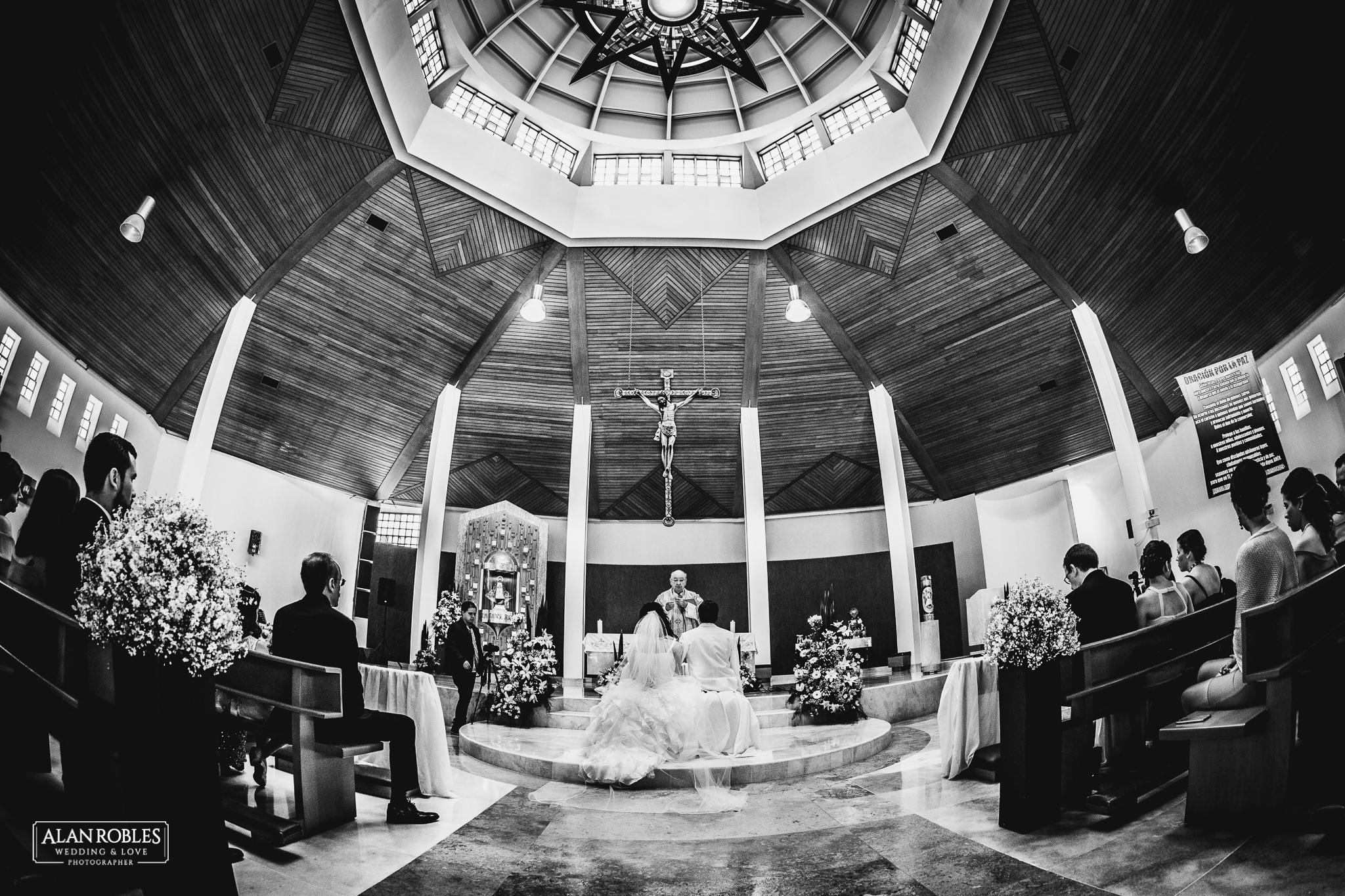 Novios en el altar casandose en Parroquia de Nuestra señora de las bugambilias. Fotografia de Boda. Vista del interior. Mejor fotografo de bodas Alan Robles en Guadalajara. Las mejores fotos de boda en mexico.