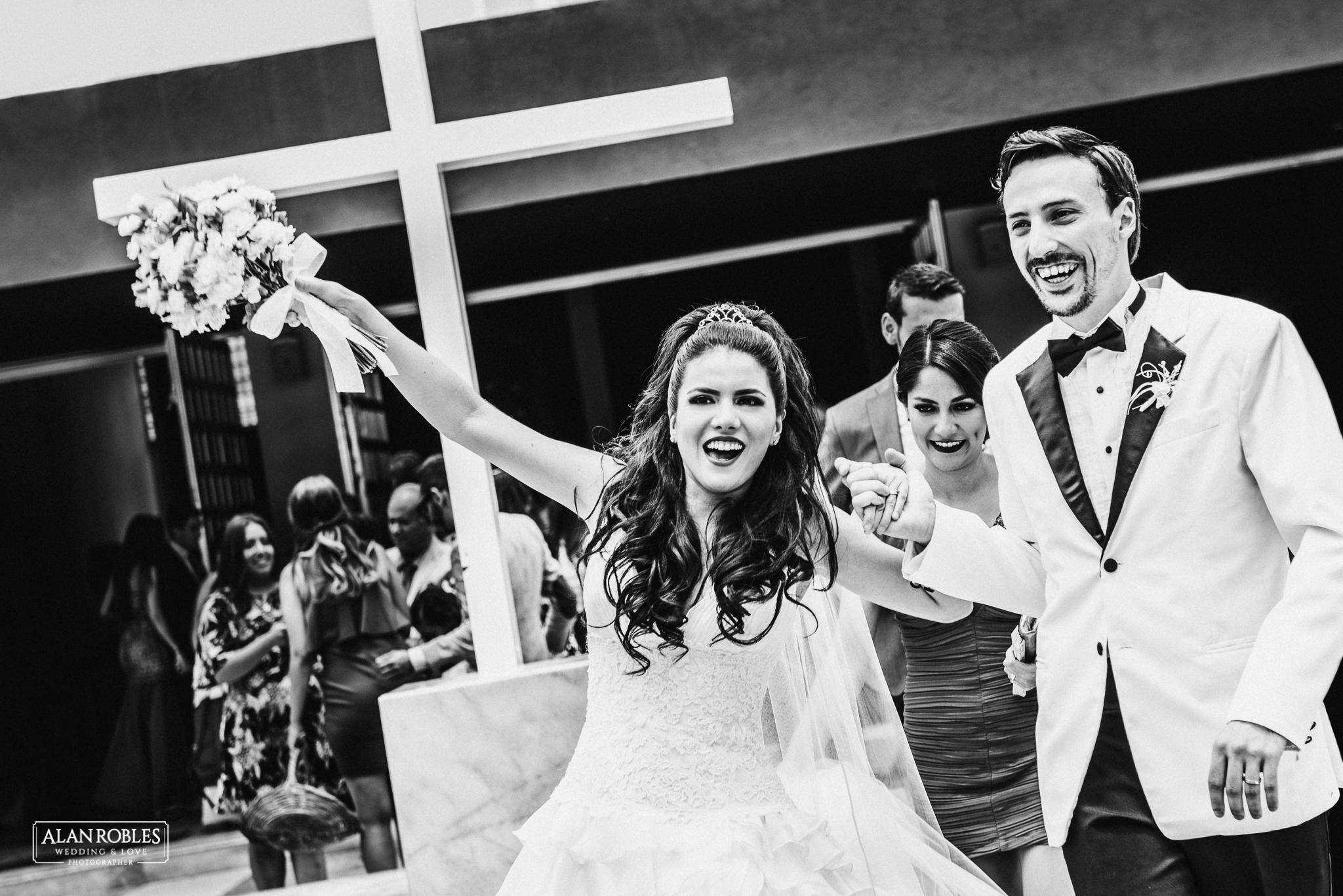 Novios festejando sonrientes, novia con ramo. Nuestra señora de las bugambilias en Guadalajara. Fotografo de bodas Alan Robles.